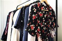 Tøjstativ med tøj til kvinder. En blomstret kimono er i forgrunden.