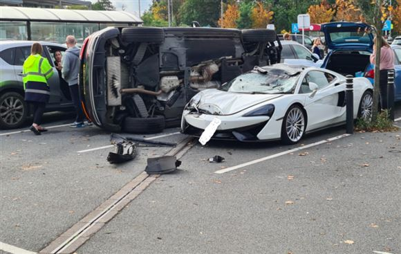 Bil ligger på siden ved siden af smadret McLaren