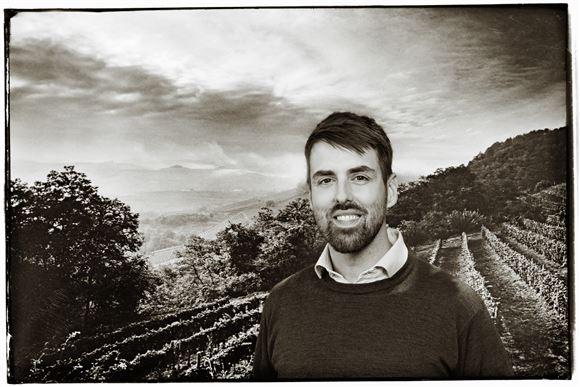 En smilende mand foran en vinmark i Frankrig.