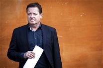 politikeren Jens Rohde står med papir i hånden op ad orange mur