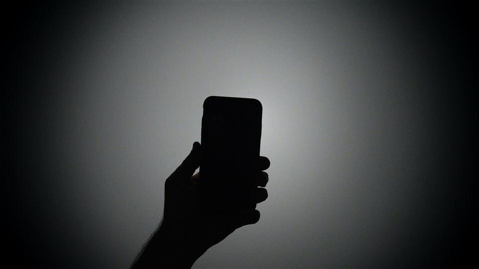 En hånd holder en telefon som for at tage et billede af sige selv. Billedet er sort hvid.
