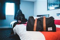 En dreng sidder på en seng med en hætte trukket over ansigtet så man ikke kan se hans identitet. I forgrunden står en taske, der er pakket.