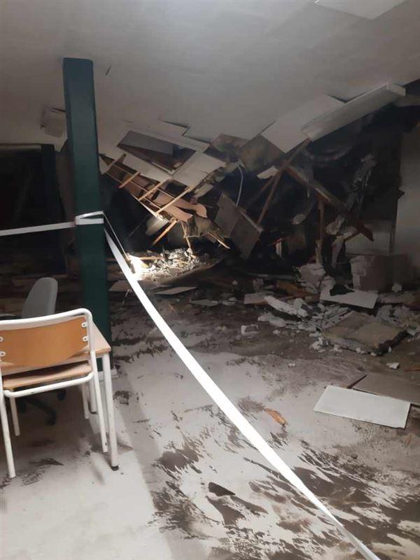 billede indefra bygningen, hvor loftet hænger og møbler er væltet omkuld.