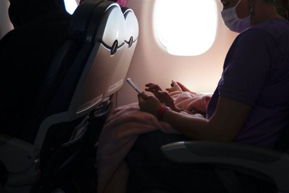 Billede inde fra et fly man ser en række personer i modlys fra flyets genkendelige runde vindue