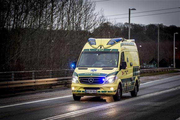 en ambulance med udrykning på en stor vej.