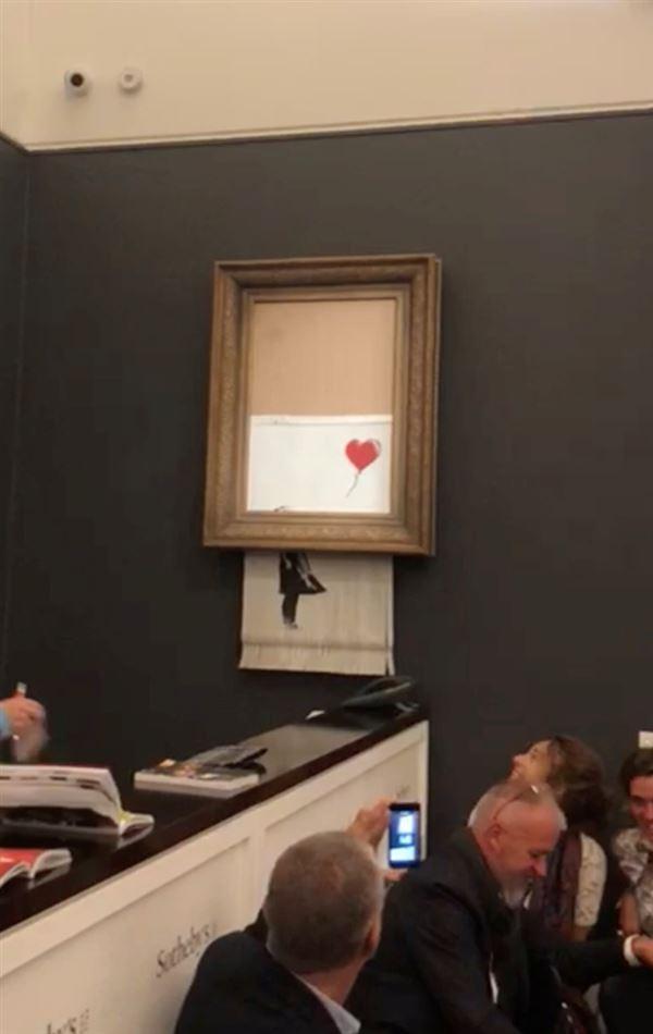 """""""Girl with Red Balloon"""" hænger makuleret på væggen"""