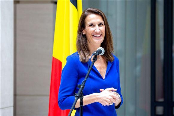 En smilende kvinde i blå bluse foran en mikrofon med det belgiske flag i baggrunden