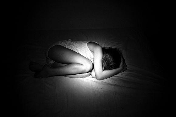 Et lille barn i fosterstilling i sengen