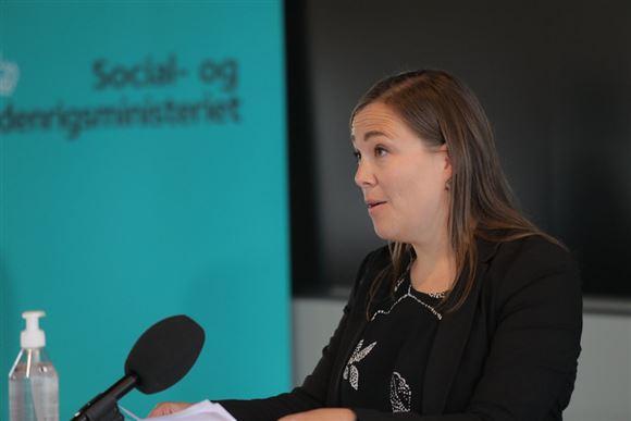 Astrid Kragh ved søndagens pressemøde. Hun ses i profil med en mikrofon foran sig.