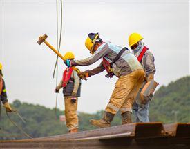 mand med hjelm og lægtehammer arbejder
