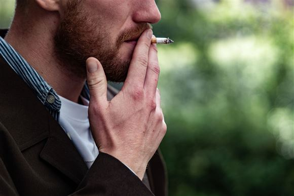 En mand ryger en cigaret