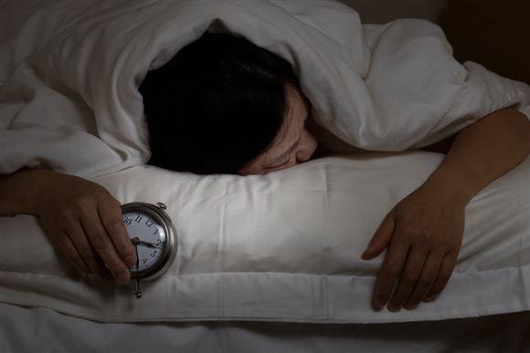En mand sover med et vækkeur i hånden