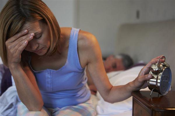 En dame sidder og tager sig på panden med et vækkeur i hånden
