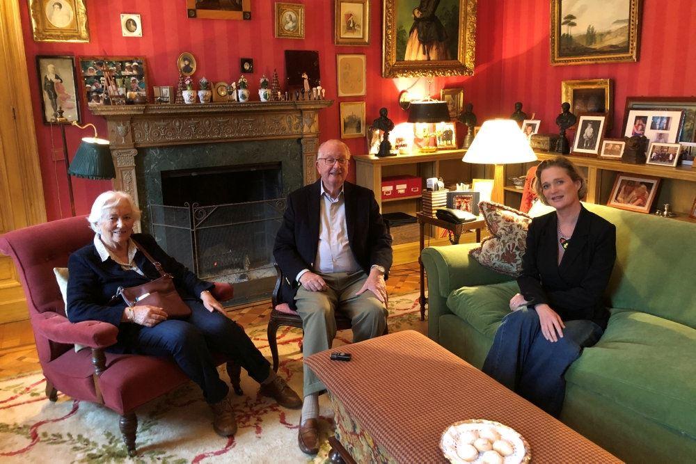 Tre personer i en elegant stue med rødde vægge