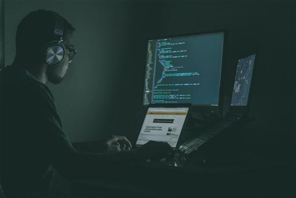 Mand sidder i mørke foran computerskærm