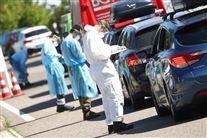 En bilkø hvor bilerne holder stille og passagerene testes for corona. Der er fire sygeplejerske der tester ad gangen.