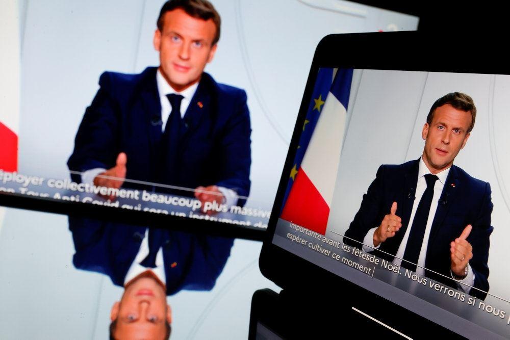 Præsident Macron holder tale til folket ved et skrivebord med det franske flag i baggrunden