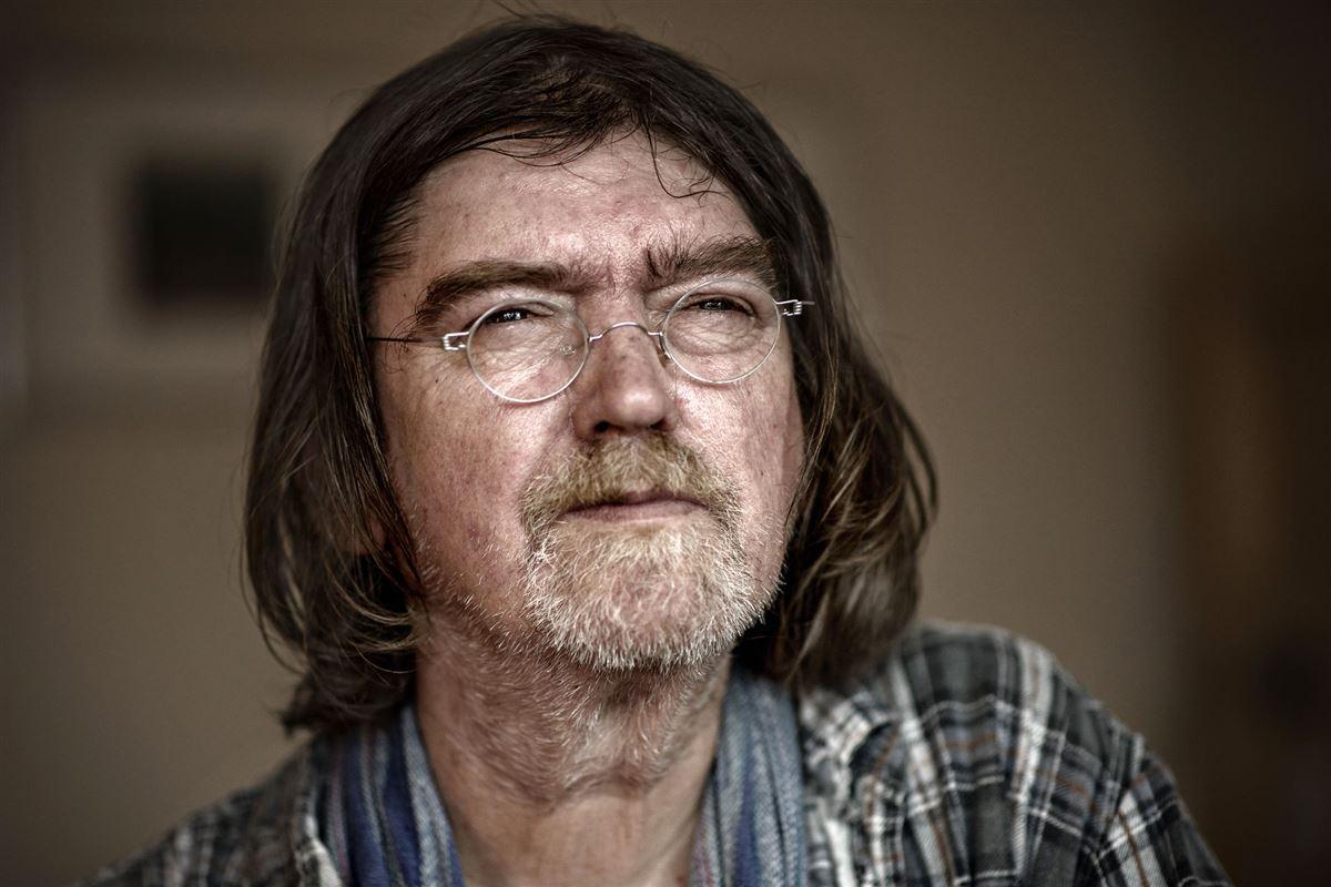 Nærbillede af Johnny Madsen med fedtet pagehår, gråt skæg og et par små nissefar briller. Han kniber øjnene lidt sammen.