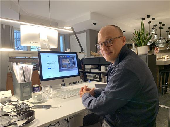 en mand med briller bag en stor skærm
