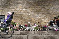 cykel med barn i barnesæde kører forbi blomster på fortovet