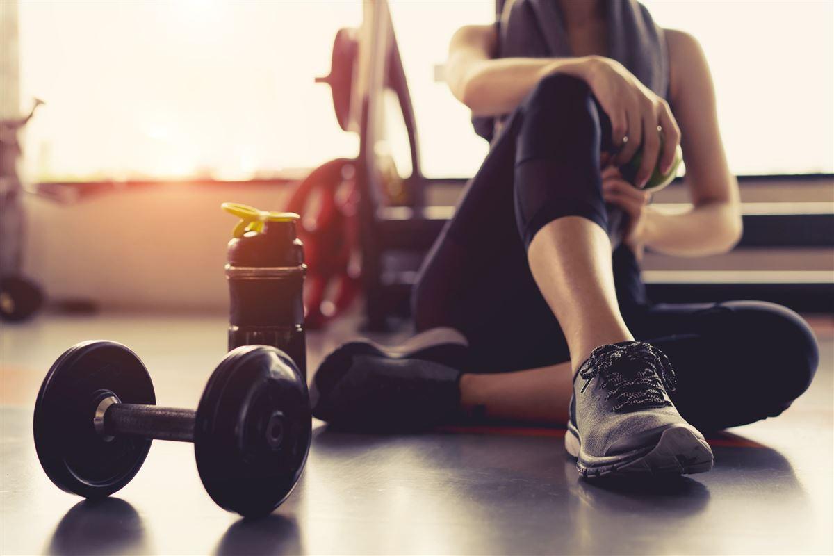 En kvinde i træningsbukser sidder på gulvet med håndvægte
