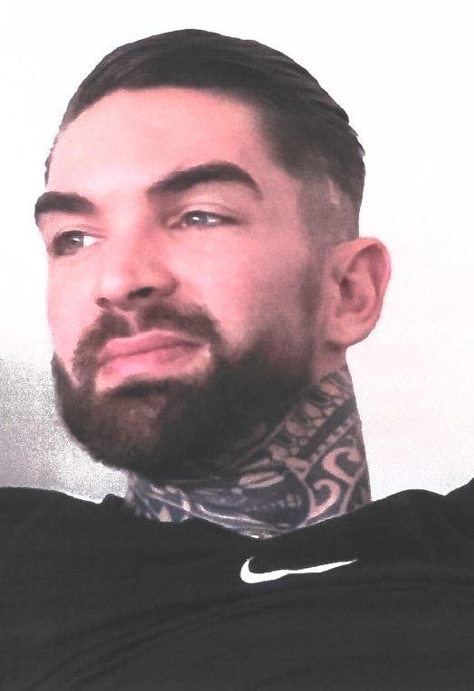 mand med fuldskæg og tatoveringer på halsen