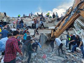 personer leder i en af de kollapsede bygninger