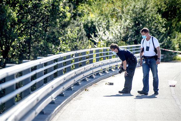 2 politibetjente med masker undersøger vejen på en bro....