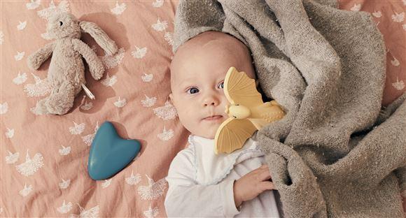 en baby med en blå elektronisk tingest ved siden af sig