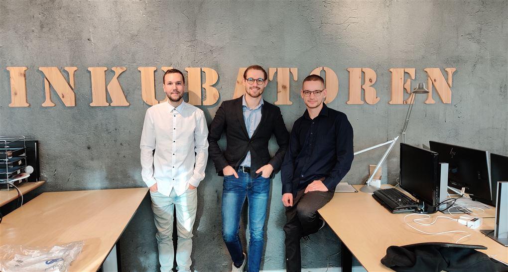 Tre unge mænd står op af en væg, hvor der står Inkubatoren