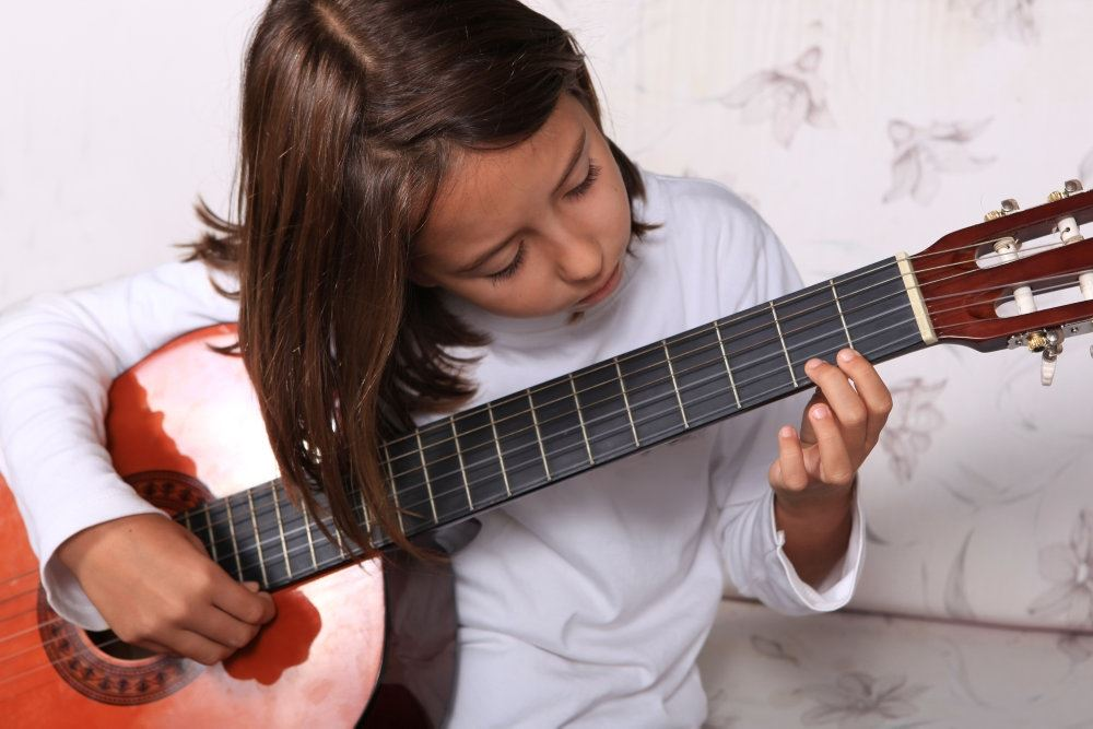 pige sidder og spiller guitar