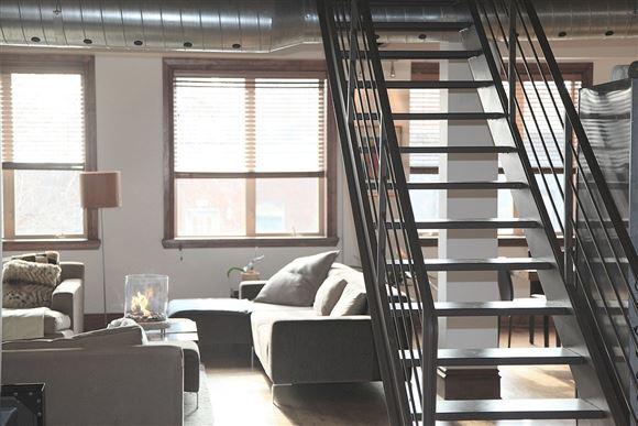 Interiør af stue med trappe til anden til etage.