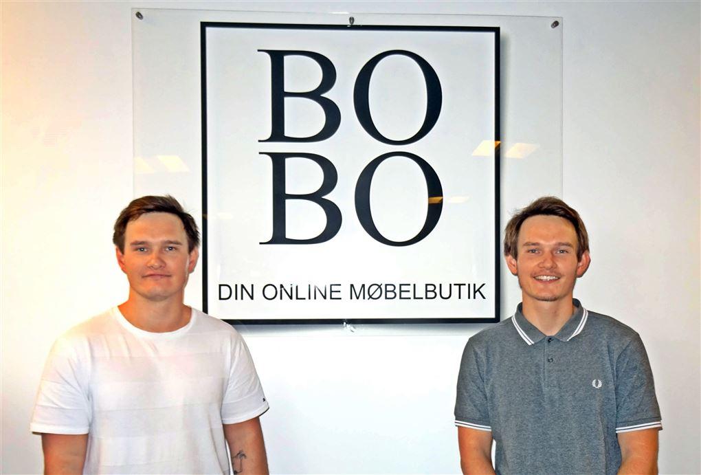 to brødre foran firmaskilt
