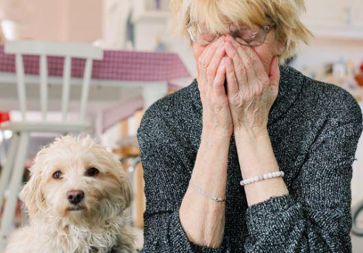 Kvinde med ansigtet i hænderne sidder ved siden af en hund