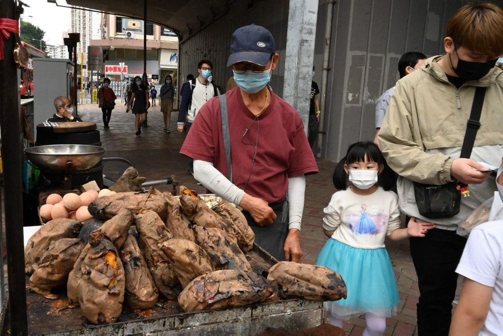 En kinesisk mand og en lille pige på et marked med mundbind på.