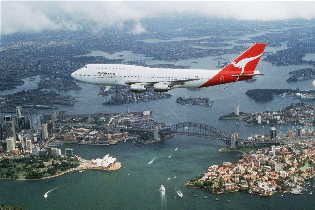 En jumbojet flyver hen over Sydney havn med operahuset og broen nedenunder.