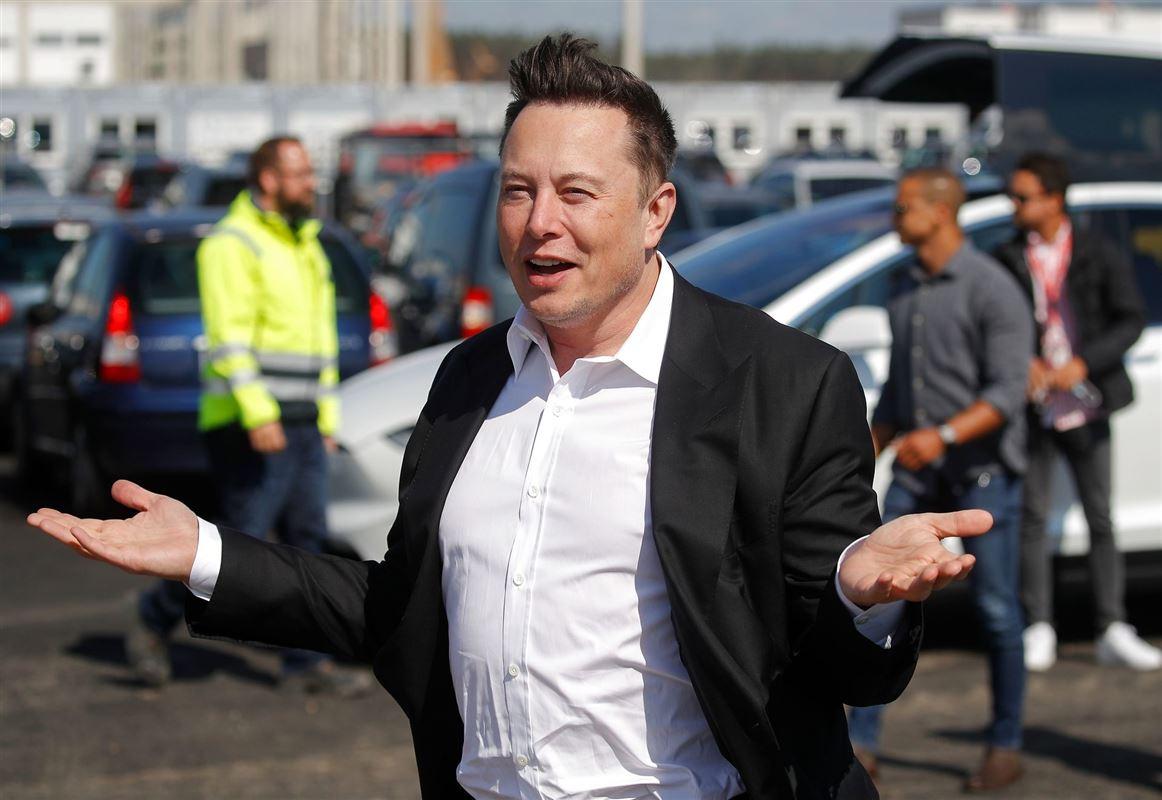 Elon Musk smiler og slår ud med armene