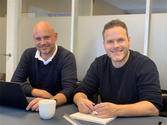 To smilende mænd ved et bord