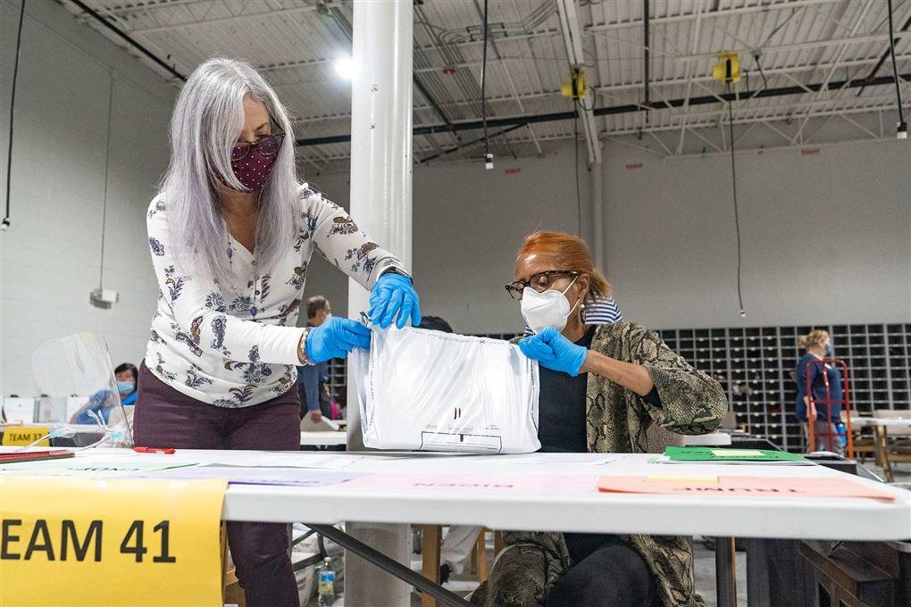 to kvinder med masker står ved skrivebord med papirbunke