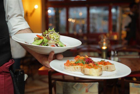 En tjener serverer to tallerkener med mad