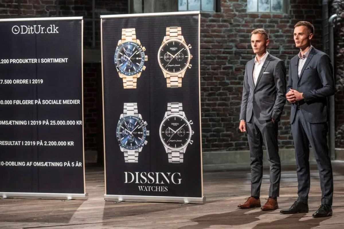 Tvillinger i jakkesæt præsenterer deres ure på en planche i et studie