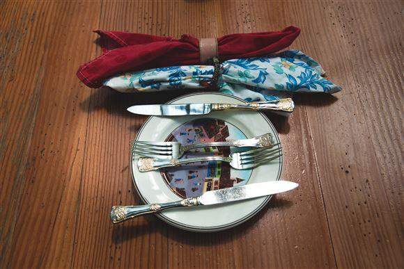 En tallerken med to gafler og to knive og to stofservietter foldet fint i servietringe.