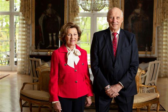 Portræt af dronning Sonja og kong Harald. Sonja er i en postkasserød blazer med en hvid skjorte under. Kongen er iført jakkesæt.