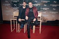 """Hans Pilgaard sammen med sin mand Jobbe til premiere på filmen """"Retfærdighedens ryttere"""". På grund af corona-restriktioner sidder parret ned på den røde løber på nogle høje barstole - på den måde kan de fotograferes uden mundbind."""
