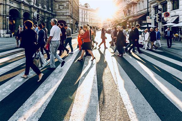 folk på gade går over fodgængerfelt