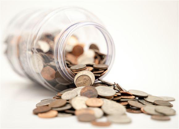 En glaskrukke med mønter væltet