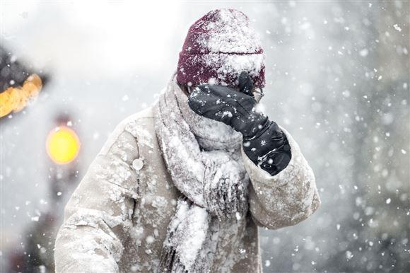 Mand med hue og halstørklæde kæmper sig frem i sneen.