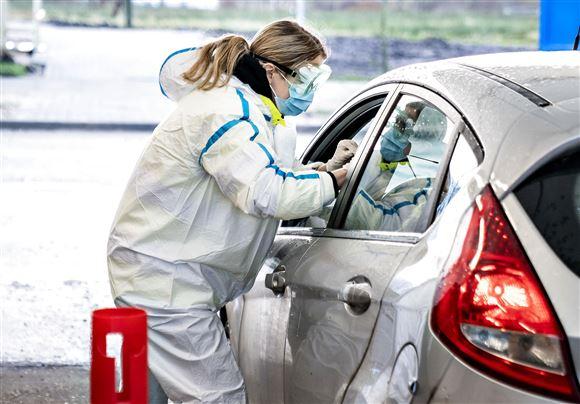 En dame i beskyttelsesdragt laver en prøve på en bilist