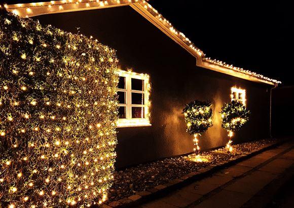 Et hus med sort facade og julelys omkring vinduerne og i buskene uden foran