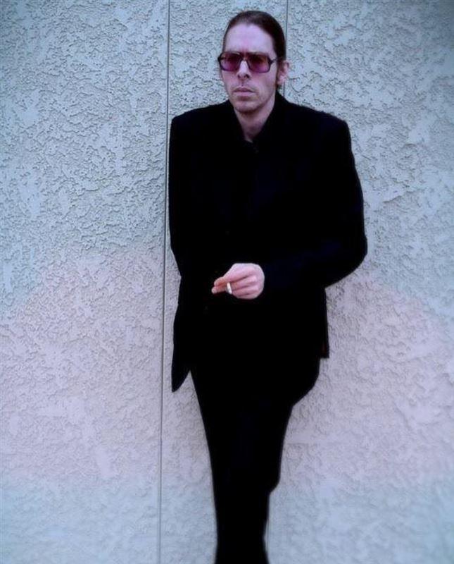 En mand med solbriller klædt i sort tøj